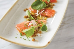 Salmon crudo of Fried Lentils, Calabrian Chili, Watercress dressed with Lemon-Ramp Vinaigrette, served on a rectangular contemporary white plate on a marble table.